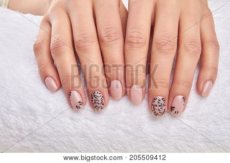 Well-groomed female hands on a white towel. Woman hands with beautiful nail design. Nails care and treatment.
