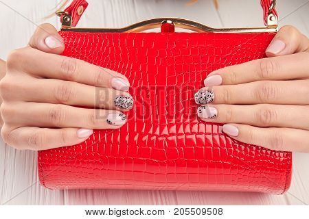 Elegant red ladies handbag in female hands. Trendy nude manicure with black lace. Womans beauty and style.