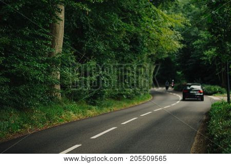 Cars Driving On The Asphalt Road Passing Through The Green Forest In The Region Of Normandy, France.
