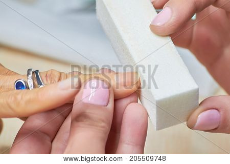 Manicure nail buffering close up. Manicure process in a beauty salon, nail beautician using nail buffer.