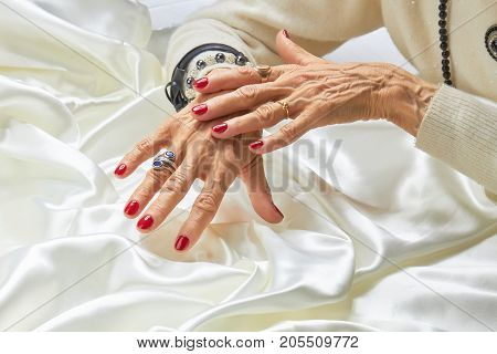 Luxury manicured hands of senior woman. Elderly woman hands with red nails and expensive jewelry on white silk background. Concept of aristocratism and prosperity.