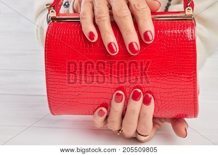 Elegant red handbag in female hands. Elderly woman hands with red manicure holding lacquered handbag close up. Womans modern accessory.