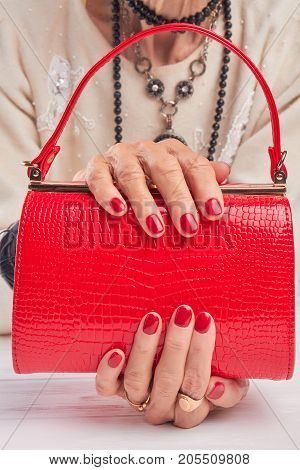 Beautiful red handbag in female hands. Woman hands with red manicure holding red leather hanbag. Female fashion accessory.