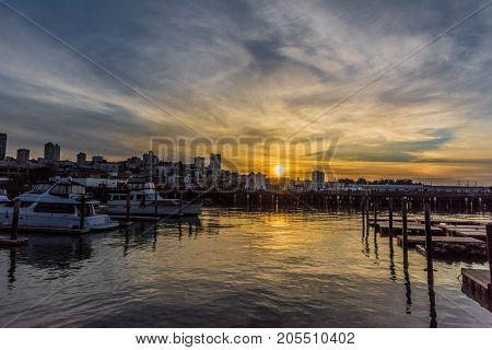Sunset at a dock in the San Francisco Bay, beautiful sunset sky, dock and boats with a reflection of the sun in the water