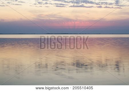 Scarlet sunset and calm waves on the lake