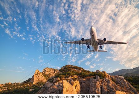Big White Airplane Is Flying Over Rocks At Sunrise