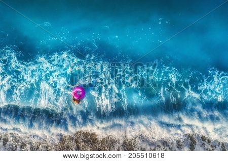 Aerial view of young woman with pink swim ring in the transparent turquoise sea in OludenizTurkey. Summer seascape with girl beautiful waves blue water in sunny morning. Top view from drone. Travel