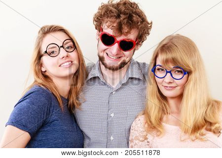 Happy playful young man in heart shaped glasses. Smiling hipster friends women and guy having fun.