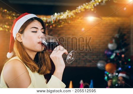 Asian teenage girl holding a glass of wine. And lift up a glass of wine to drink with friends. Her party the Christmas and New Year's Day.