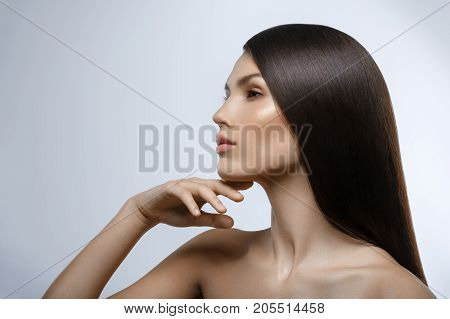 beautiful young woman with natural glowing makeup and long straight hair. beauty shot on gray background. hand touching face. copy space.