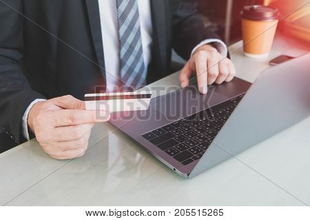 Businessman shopping online with credit card and laptop in home office or co working space.Concept of e-commerce using mobile technology.