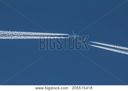 Two passengers jets are flying to each other in blue sky, telephoto shot