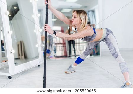 Attractive blonde sportswoman doing stretching exercise standing feet wide apart leaning forward resting on body bar in fitness club.