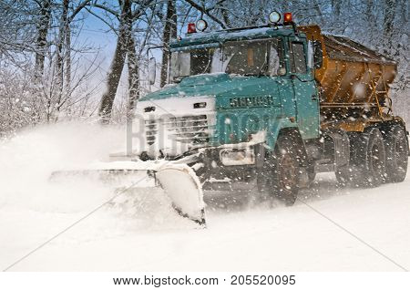 a snow plow doing snow removal during blizzard