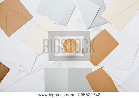Cup of coffee with mail envelopes pattern top view. Lifestyle correspondence concept background. Flat lay style.