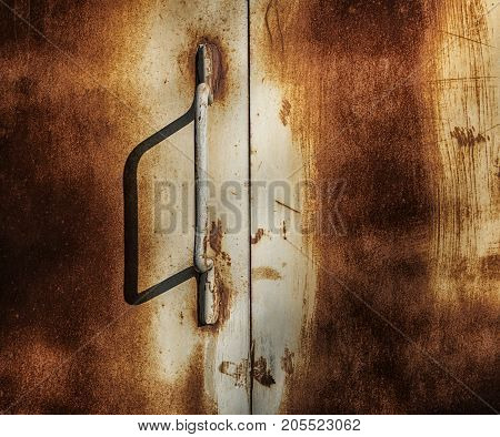 Rusty door. Rusty metal door. Grunge rusty door. Grunge metal background. Grunge metal texture. Grunge metal. Grunge pattern. Grunge style. Abstract background rusty surface. Grunge background.