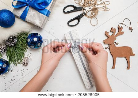 Holiday preparation. Christmas and New Year. Unrecognizable woman wrapping present box, handmade wooden deer, ornament blue balls and pine branch with scissor laying on table nearby, top view