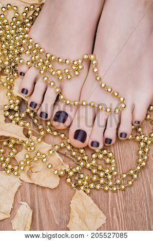 Female feet with dark purple pedicure on wooden background. Fall pedicure.