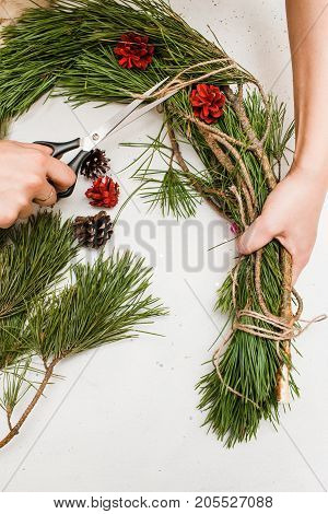 Christmas wreath making by woman, top view. New Year holidays, festive decoration from pine and strobila, national traditions concept