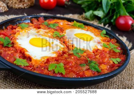 Shakshuka - a dish of eggs fried in a sauce of tomatoes hot pepper onions and seasonings. Israeli cuisine. Served for breakfast with rye bread.
