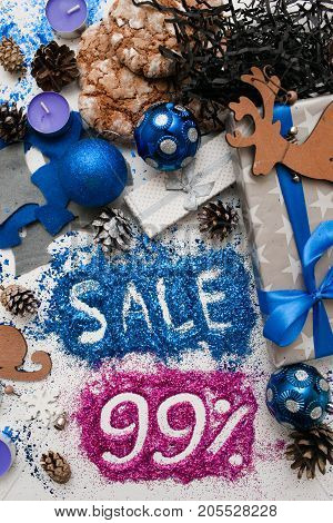 Sales on Christmas and New Year holidays, top view reversed. Festive decoration with informative inscription of 99 pct discount for shop-windows, shopping malls and advertizing background concept