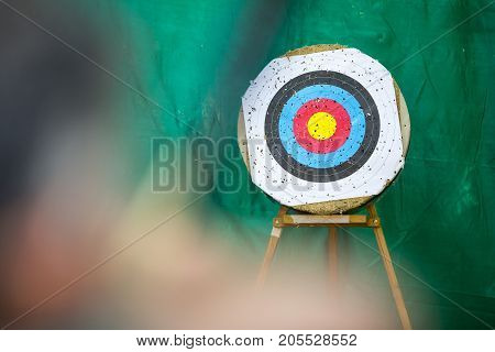 Archery target ring and out of focus archer with a bow in the foreground during an archery competition. Green background.