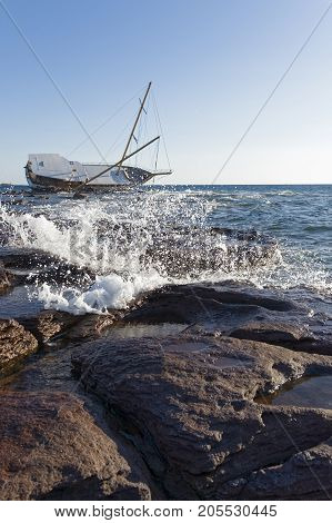 Sailboat stranded along the coast on the cliff of Sardinia in the Mediterranean Sea.