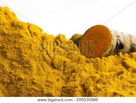 close up of turmeric used for cooking and health benefits such as anti inflammatory showing powered and root whit a with background for copy space