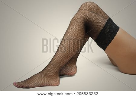 Sexy female legs in fishnet pantyhose stockings isolated.