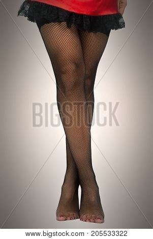 Young woman in red dress and black fishnet pantyhose stockings on her legs standing on her socks with her legs crossed isolated.