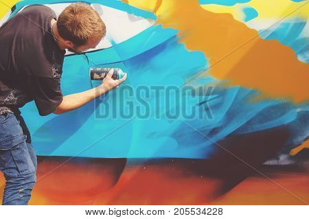 Photo in the process of drawing a graffiti pattern on an old concrete wall. Young long-haired blond guy draws an abstract drawing of different colors. Street art and vandalism concept.