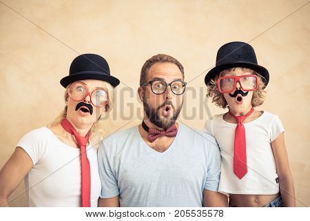Funny man woman and kid with fake mustache. Happy family playing in home