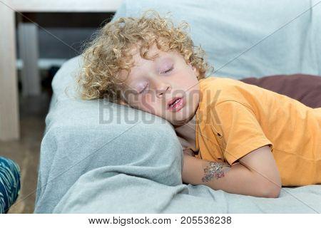 a little boy sleeping on the sofa