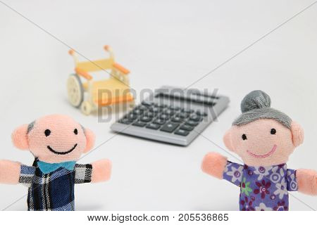 Elderly people with wheelchair and calculator on white background. Plans for retirement living concept.