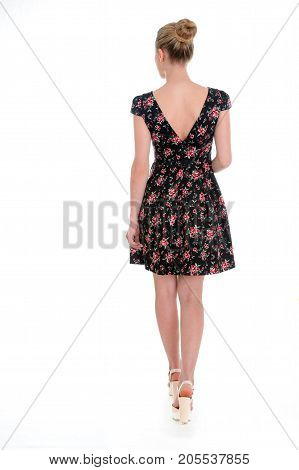 Woman in short floral dress. Wedge sandals and summer dress. Casual look for warm season. Garment made of flax.