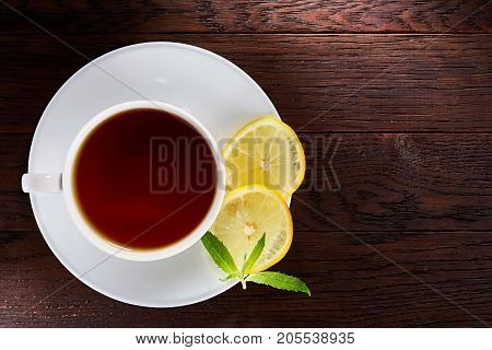 White cup of tea with saucer on a wooden background top view.