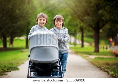 Two Children, Boys, Pushing Stroller With Little Baby