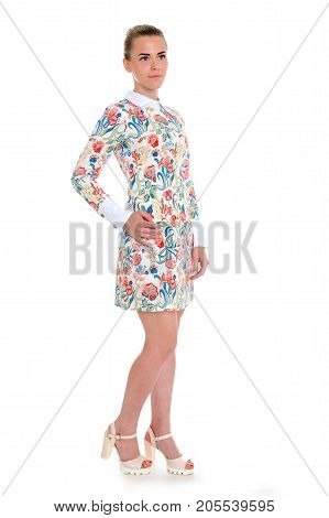 High key portrait of young elegant woman in evening dress with floral pattern.