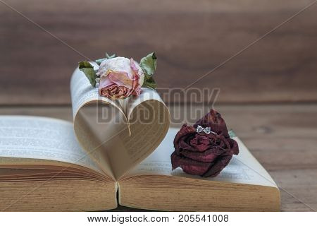 Dried red rose with diamond engagement ring making a proposal to pink rose on old heart-shape book love and marriage concept (vintage tone)