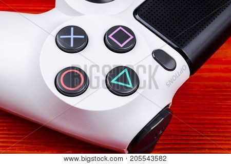 Sankt-Petersburg Russia September 24 2017: Sony PlayStation 4 Slim 1Tb revision and dualshock game controller. Game console with a joystick. Home video game console on red background
