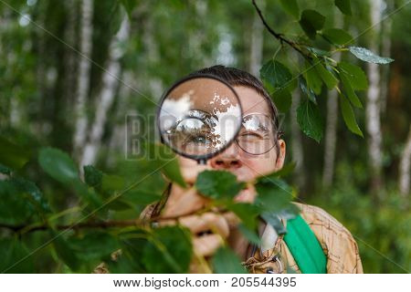 Photo of male botanist with magnifying glass in front of person in summer forest