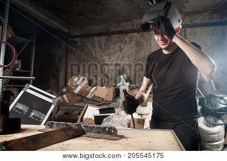 An adult man welder in a black T-shirt and a black welding mask brews a metal welding machine in a dark workshop