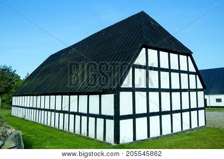 Black and white half timbered house with blue sky and green grass on a sunny day.