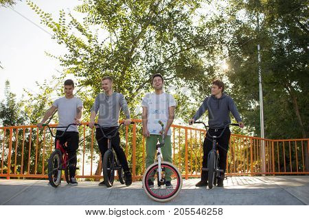 Group of young people with bmx bikes in skate plaza, stunt bicycle riders in skatepark