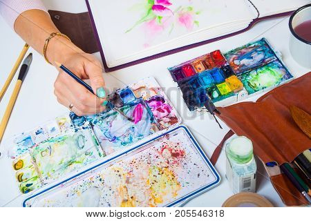 A close-up artist paints and paints in the album for drawing a thin wooden brush with pink watercolor colors on the table is a leather case with brushes watercolor palette