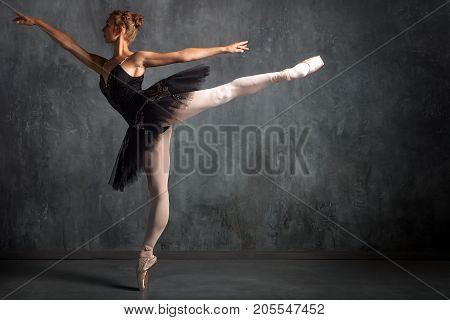 Beautiful attractive blonde woman primer ballerina in a black dance pack white pantyhose and pointe shoes beautifully dances ballet in a dark studio