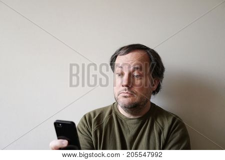 wide-eyed man looking at smartphone, sitting by wall with copy space