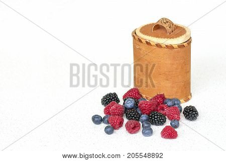 Berries variation and birch bark basket on a white background