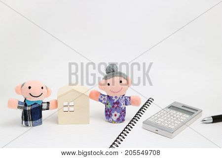 Old couple and house with calculator on white background. Plans for retirement living concept.