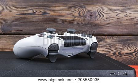 Sankt-Petersburg Russia September 24 2017: Sony PlayStation 4 Slim 1Tb revision and dualshock game controller on the wood background
